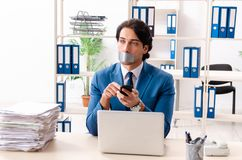 Young male employee with tape on the mouth. The young male employee with tape on the mouth royalty free stock images