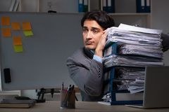 The young male employee working late at office stock photo