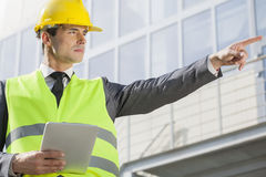 Young male engineer with digital tablet pointing away outside industry Stock Photo