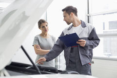 Young male engineer explaining car engine to female customer in workshop Royalty Free Stock Photo