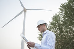 Young male engineer in a hardhat looking down at a blueprint in front of a wind turbine Stock Photography
