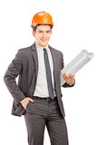 Young male engineer with helmet holding blueprints Royalty Free Stock Photo