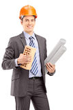 Young male engineer holding a brick and a blueprint Stock Image