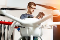 Young Male Engineer or Technician with Holding Tablet in His Hands Programs Drone. Young Male Engineer or Technician with Holding Tablet in His Hands Programs Stock Photography