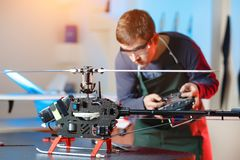 Young Male Engineer or Technician with Remote Control in His Hands Programs Drone. Focus on Drone. Young Male Engineer or Technician with Remote Control in His royalty free stock image