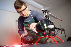 Young Male Engineer or Technician with Remote Control in His Hands Programs Drone. Young Male Engineer or Technician with Remote Control in His Hands Programs Royalty Free Stock Photo