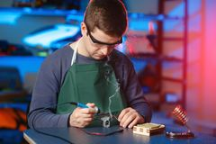 Young Male Engineer or Technician Repair Soldering Drone Details. Young Male Engineer or Technician Repair Soldering Drone Details Royalty Free Stock Images