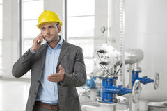 Young male engineer using cell phone in industry Royalty Free Stock Photos