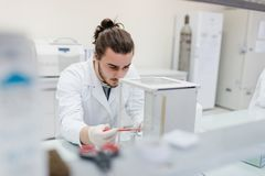 Young male engineering student doing an experiment in genetics l. Aboratory by himself in laboratory Royalty Free Stock Images
