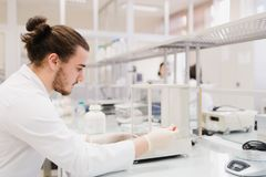 Young male engineering student doing an experiment in genetics l. Aboratory by himself in laboratory Stock Photo