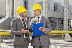 Young male engineers with clipboard discussing at construction site Stock Photos