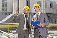 Young male engineers with clipboard discussing outside industry Stock Images