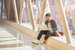 Young male entrepeneur student waiting working on laptop in sunn Royalty Free Stock Photo
