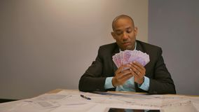 Young male entrepreneur counting money at his desk. Portrait. Looking at camera. He hold it like fan stock video