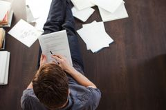 Young male entrepreneur makes brainstorming sitting on the floor in the apartment. Creative approach to business. Young male entrepreneur makes brainstorming Royalty Free Stock Photos