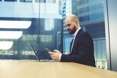 Young male entrepreneur is searching on web site information via cell telephone. Intelligent businessman is reading text message on mobile phone, while is Royalty Free Stock Photo