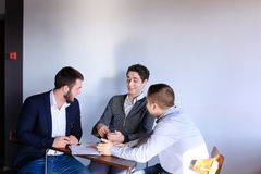 Young male entrepreneurs and partners are engaged in solving bus Royalty Free Stock Photos