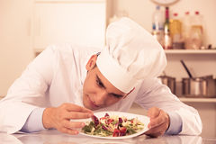 Young male is evaluating prepared dish. On kitchen Royalty Free Stock Photo