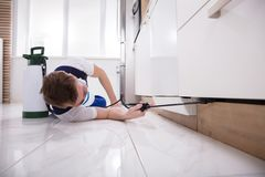 Exterminator Worker Spraying Insecticide Chemical. Young Male Exterminator Worker Spraying Insecticide Chemical In Kitchen Royalty Free Stock Photo