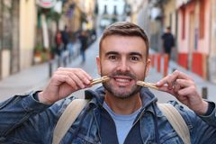 Young male faking a smile with clothespins.  royalty free stock images