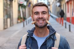 Young male faking smile with clothespins.  stock photo