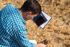 Young male farmer agronomist botanist studies mowed hay with a magnifying glass and a tablet in the field view from the back. Young male farmer agronomist royalty free stock images