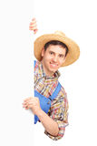 Young male farmer holding a white panel. Isolated on white background Royalty Free Stock Photo