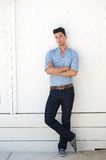 Young male fashion model in blue jeans and shirt. Portrait of an attractive young male fashion model in blue jeans and shirt standing against white wall outdoors Stock Photography