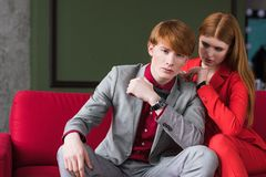Young male fashion model with girlfriend. Sitting on couch royalty free stock image
