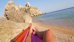 Young Male Feet Swinging in a Hammock on the Beach, POV. Relaxing Carefree Man Resting and Sunbathing near Beautiful Sea. HD Slowmotion. Crimea stock video