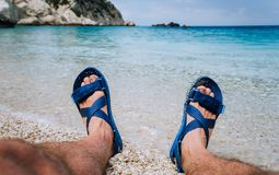 Young male feet wear blue flip-flop sandal sunbathing on pebble beach in front of blue sea water and rocks in background. On horizon stock images