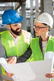 Young male and female architects or business partners discussing floor plans on a construction site, facing each other royalty free stock photo