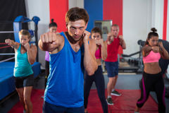 Young male and female athletes punching by boxing ring stock photo