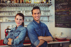 Young male and female baristas at cafeteria. Young male and female baristas standing with arms crossed at cafeteria Royalty Free Stock Images