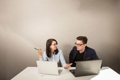 Young male and female business partners sitting behind a computer monitor and thinking of something stock image