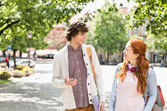 Young male and female college students talking while walking on footpath Stock Photography