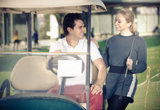 Young male and female golf players are enjoying game Royalty Free Stock Image