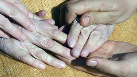 A young male and female hands comforting a old pair of hands outdoor. Royalty Free Stock Photo
