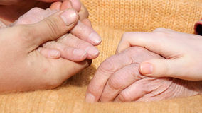 A young male and female hands comforting a old pair of hands outdoor. Stock Photo