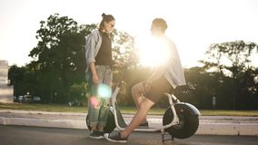 Young male and female are have time together outdoors. Boy`s sitting on an electro mini bike and smiling. The girl in