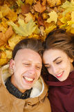 Young male and female having good time. Young male and female lying down on yellow maple leaves smiling happy having good time Stock Photo