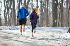 Young male and female jogging in nature, back view. Young male and female jogging in nature at winter, back view Royalty Free Stock Photos