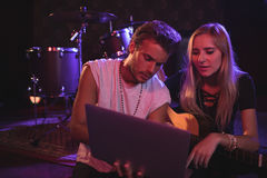 Young male and female musicians using laptop in nightclub. Young male and female musicians using laptop while practicing in nightclub Royalty Free Stock Images