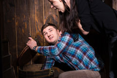Young male and female opened a barrel and trying to solve a conu Royalty Free Stock Image