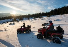 Young male and female riders on quad bikes on snow, enjoying sunset in the the mountains in winter. Young male and female riders sitting on quad bikes on snow Stock Photography