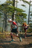Young male and female runners in woods ran uphill Stock Image