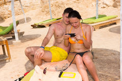 Young male and female sitting on a sun lounger after swimming in. The sea, wearing swimsuits and watching at the phone Royalty Free Stock Photography