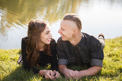 Young male and female smiling. Young male and female lying down on grass near water talking smiling looking at each other Royalty Free Stock Photography