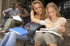 Young male and female students studying on the steps. Royalty Free Stock Photography