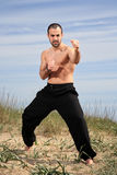 Young male fighter exercise outdoor. Young male fighter exercising on a sand hill Stock Images